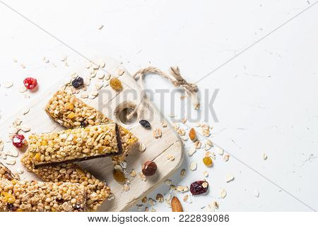 Granola bar with nuts, fruit and berries on a white stone table. Top view copy space.