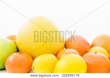 Fruit's background. Citrus fruits pattern made of lemon, orange, grapefruit, sweetie and pomelo on white background.