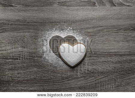 on a wooden background with powdered powder snow a silhouette of the heart is poured and below on the silhouette lies a cookie in the form of a heart
