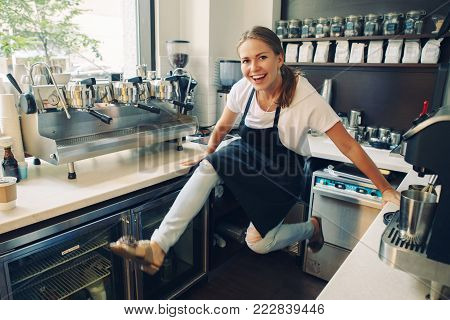 Young Caucasian barista laughing having fun jumping at work place. Small business concept