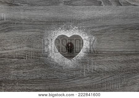 on a wooden background with powdered powder, a silhouette of the heart is poured with snow and in the center lies chocolate round candy