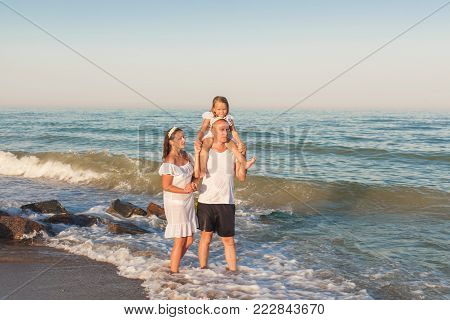 Dad, mom and daughter are walking along the seashore. Dad carries daughter on his neck