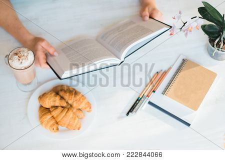 Top of hand holding and opening blank book or magazine for reading with glass of macchiato coffee on wooden table in cafe.