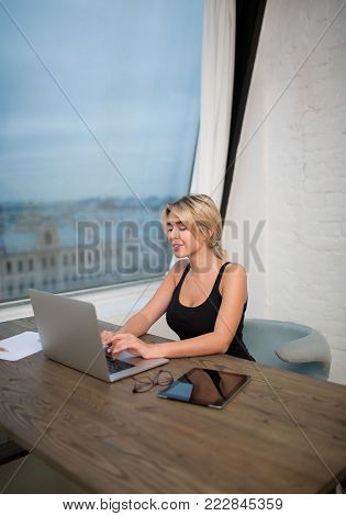 Woman confident business coach  searching information on web site, sitting at workplace with laptop computer. Female CEO working on modern net-book, sitting near office window. Student using notebook