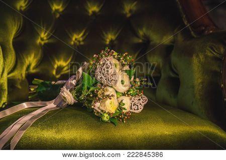 white wedding bouquet on a antic green velvet chair