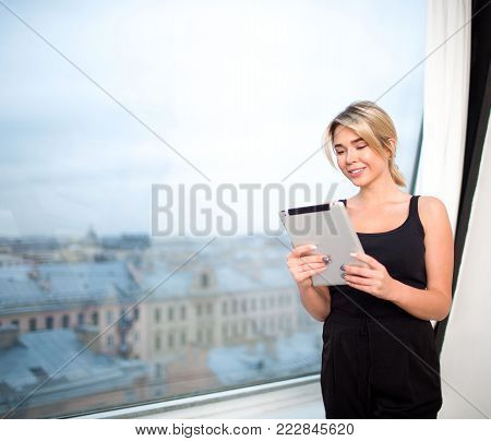 Smiling businesswoman having on-line video call on touch pad, standing near office window with copy space. Cheerful female skilled manager reading news in network via portable digital tablet