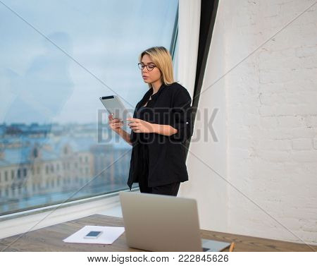 Young successful woman development specialist using digital tablet, standing in office near workspace with laptop computer. Female proud CEO reading financial news in internet via portable touch pad