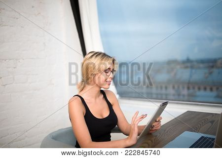 Smiling woman magazine editor having video call on-line via touch pad, siting at work table with laptop computer. Cheerful hipster girl skilled freelancer using digital tablet for chat in network