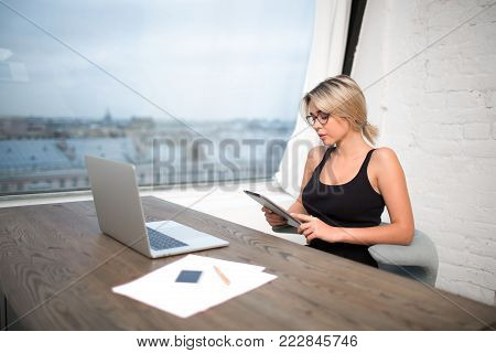 Young successful businesswoman reading contract on touch pad, sitting at the table with open net-book and paper documents against window with copy space. Female project manager using digital tablet