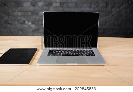Workstation with digital tablet, open laptop computer with empty copy space screen for advertising text. Desktop with touch pad and portable net-book. Modern workspace with gadgets