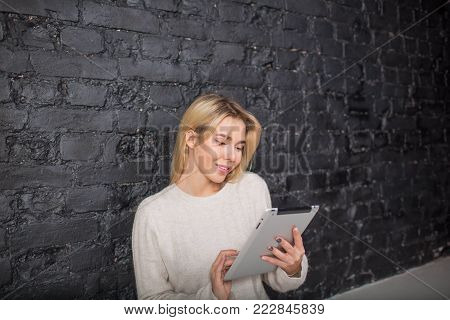 Amazing woman manger searching information in internet on touch pad, sitting against brick wall with copy space. Cheerful female developer sites using portable digital tablet. Student reading e-book