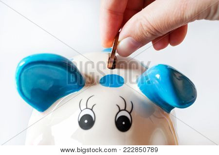 economy and finance - savings in a money box - piggy bank and hand with coin
