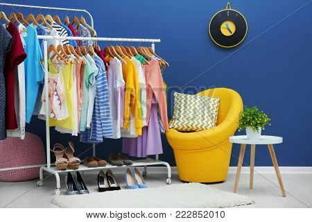 Neat dressing room interior with clothes rack and stylish armchair
