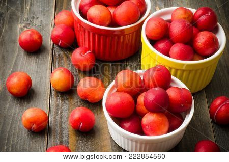 Ripe plum fruit (Julee) on wooden background