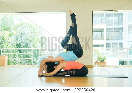 Young asian women practicing yoga, fitness stretching flexibility pose, working out, healthy lifestyle, wellness, well being