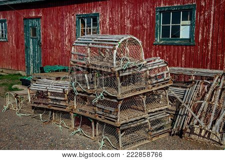 Lobster traps in front of an old red shed.