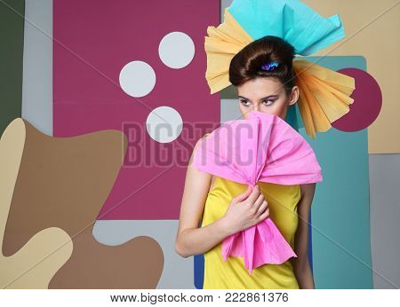 A female model in yellow is actively posing in the studio on an unusual background. Fashion story, Danish design. Color composition. Eccentric attire. Short dress, pink bow of paper in hand.