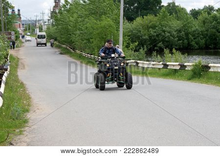 Man on the ATV Quad Bike on the mountains road. Russia Usolye July 1, 2017 .