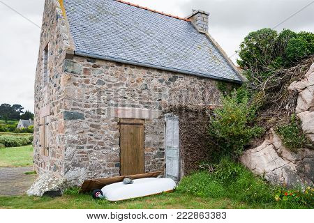 travel in France - typical stone Breton house in Plougrescant town of the Cotes-d'Armor department in Brittany in rainy summer day