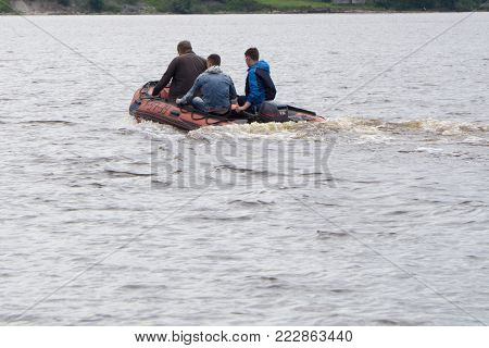 three unidentified man in a red cloak, runs red inflatable  boat with outboard motor on lake blue fall forest on a Sunny day