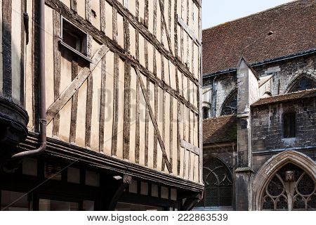 travel to France - old half-timbered house on street Rue Champeaux and wall of church Eglise Saint-Jean-au-Marche in Troyes city