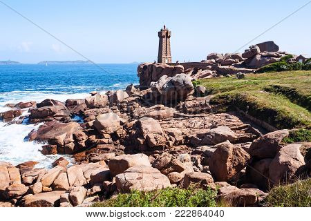 travel to France - Mean Ruz lighthouse in Ploumanac'h site on coast of English Channel in Perros-Guirec commune on Pink Granite Coast of Cotes-d'Armor department of Brittany in sunny summer day