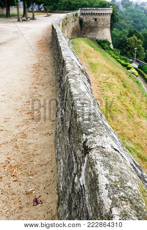 travel to France - city wall along belvedere at Promenade de la Duchesse Anne of the Jardin Anglais ( English garden) in Dinan town in rain