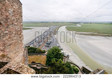 Travel to France - above view of car parking and the causeway to Le Mont Saint-Michel island in Normandy in rain