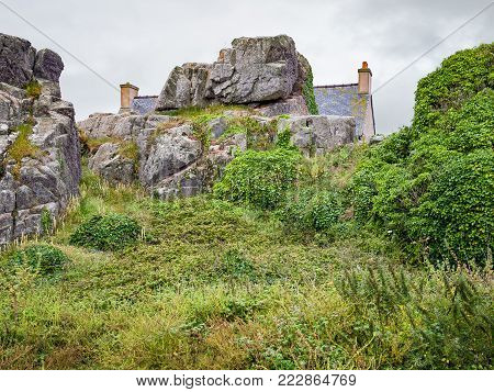 travel in France - rock and stone Breton house in Plougrescant town of the Cotes-d'Armor department in Brittany in rainy summer day