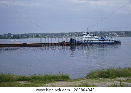 loaded tug pushing a barge on the river .