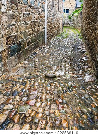 travel to France - wet pavement of narrow street in Treguier town in the Cotes-d'Armor department of Brittany in summer rainy day