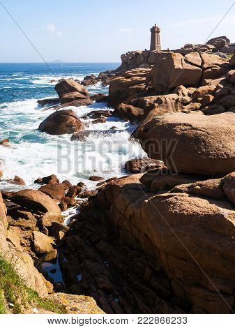 travel to France - rocky coast of English Channel with lighthouse in Ploumanac'h site of Perros-Guirec commune on Pink Granite Coast of Cotes-d'Armor department of Brittany in sunny summer day