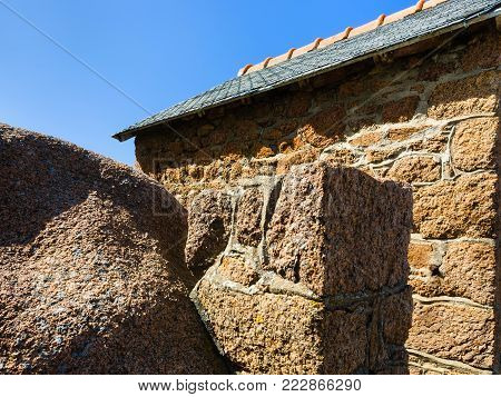 travel to France - granite boulder and wall of breton stone house in Ploumanac'h site of Perros-Guirec commune on Pink Granite Coast of Cotes-d'Armor department of Brittany in sunny summer day