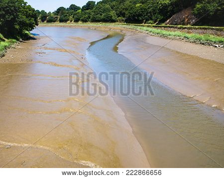 travel to France - muddy riverbank of Jaudy river in Cotes-d'Armor department of Brittany in sunny summer day