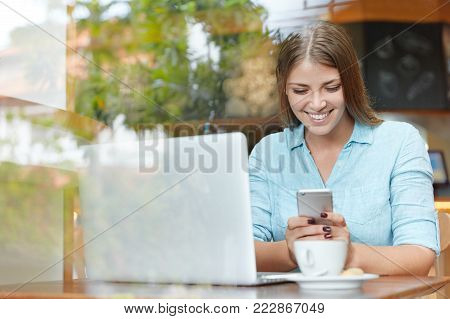 Pretty Young Female Model With Long Hair, Browses Internet Websites On Laptop Computer, Connected To