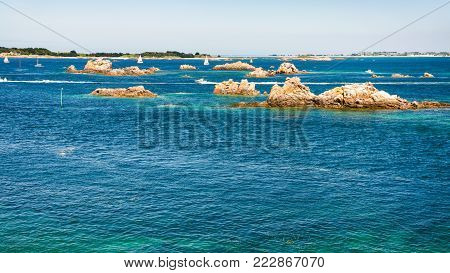 travel to France - above view of granite rocks in ocean near coast of Ile-de-Brehat island in Cotes-d'Armor department of Brittany in summer sunny day
