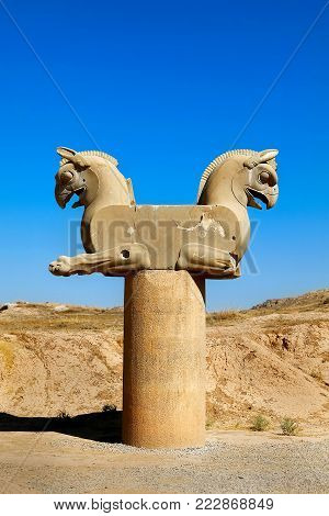 Stone column sculpture of a Griffin in Persepolis against a blue clear sky. The Victory symbol of the ancient Achaemenid Kingdom. Iran. Persia. Shiraz.