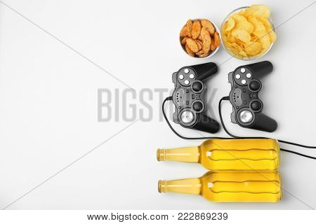 Composition with video game controllers, beer and snack on light background