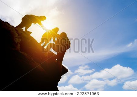Asia couple hiking help each other silhouette in mountains with sunlight, Couple hiking help each other silhouette in mountains with sunlight