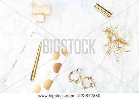 Notebook c of office items of gold color and cosmetics on the desktop. Copy space