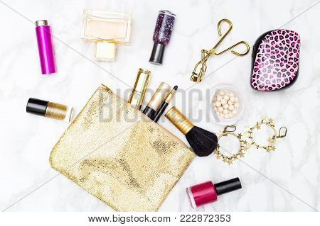Makeup and accessories gold and pink for girls on the table. Flat lay