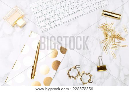 Keyboard c of office items of gold color and cosmetics on the desktop of the house. Flat lay