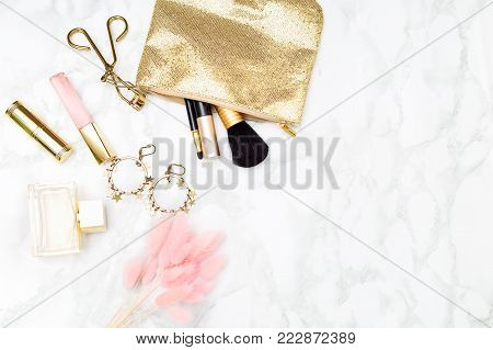 Makeup gold & blush on the desk. Gold styled stock copy space