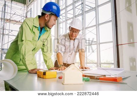 engineers, technician and architect planning start up new project about building plan with blueprint and construction tools on conference table at construction site, business and industry concept