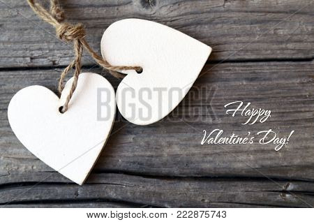 Happy Valentine's Day.Decorative white wooden hearts on rustic wooden background.St Valentine's Day or Love concept.Selective focus.