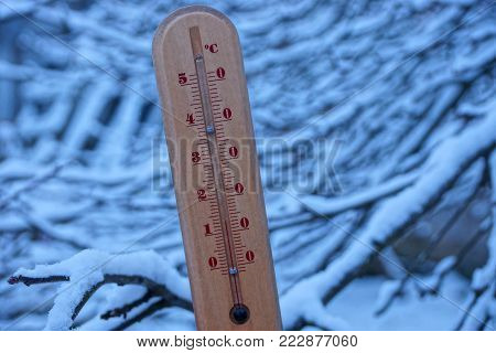 wooden thermometer on the street against the background of branches in the snow
