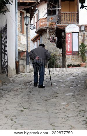 Old man walks up the narrow street in the Old Town of Veliko Tarnovo in Bulgaria