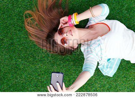 Beautiful young woman making selfie by her phone while lying in green grass. Beautiful young woman making selfie