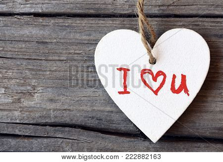 Valentines Day holiday background.Decorative white wooden heart with I love You inscription.I Love You,St Valentine's Day or Love concept with copy space.