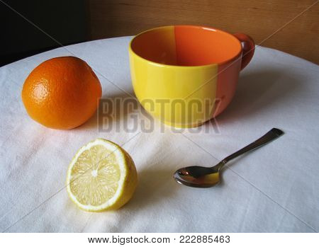 Still life. Orange, lemon, cup and spoon on a white tablecloth. Harmoniously   and attractively look objects in orange and yellow colors, reflecting on the   glossy surface of the spoon and contrasting with a white tablecloth.